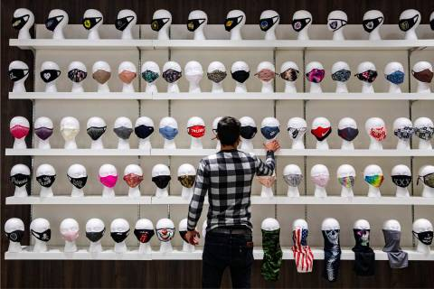 Salesperson Lucas Nascimento rearranges masks for sale at the COVID-19 Essentials store in the ...