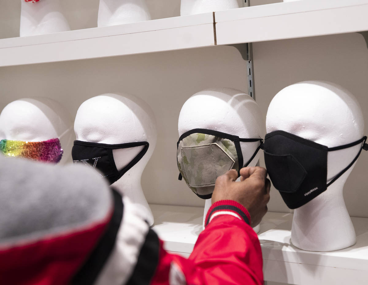 Costa Collins, of Atlanta, checks out a mask for sale at the COVID-19 Essentials store in the F ...