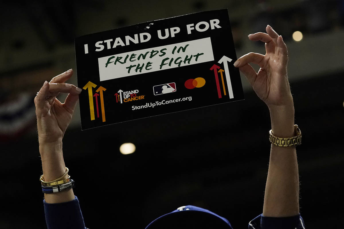 """A fan participates a """"Stand Up to Cancer"""" moment during in Game 3 of the baseball Wor ..."""