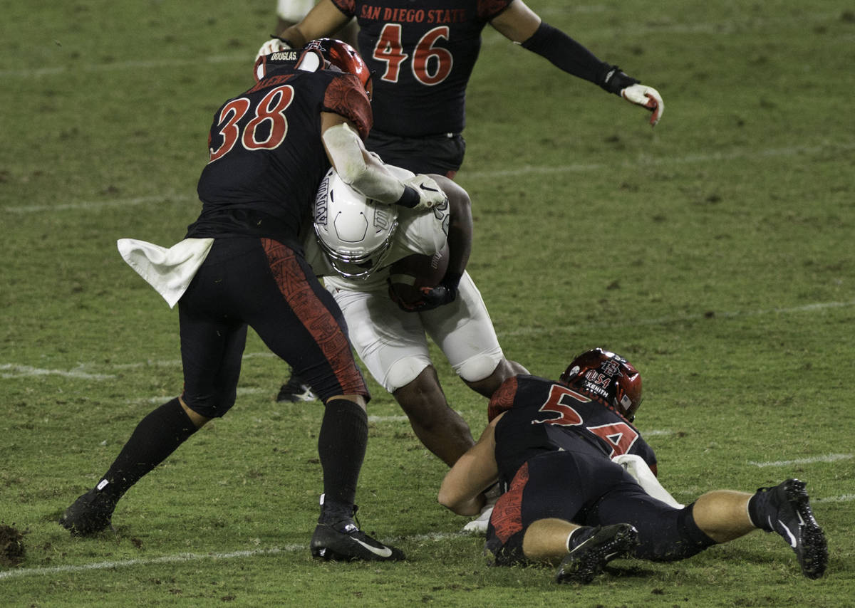 San Diego State's Andrew Aleki (38) and Caden McDonald tackle UNLV's Dylan Downing during S ...