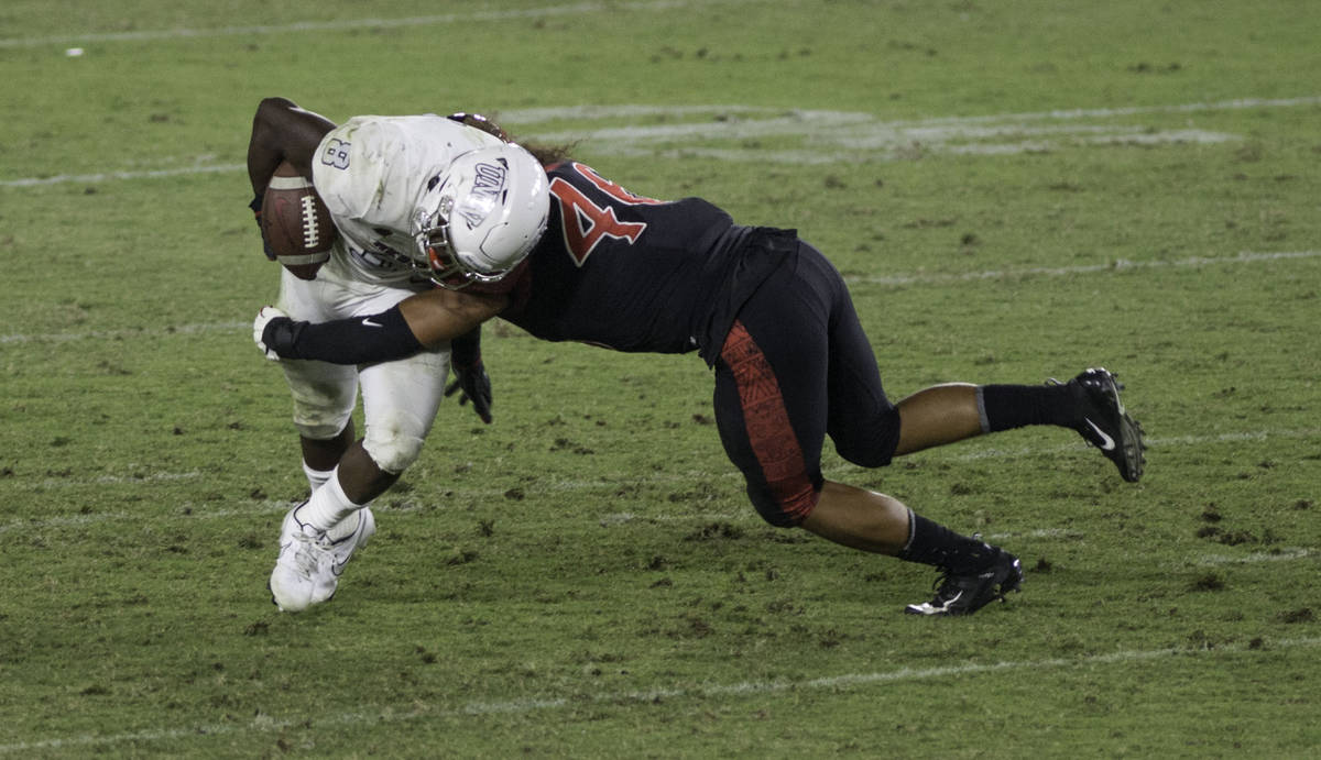 UNLV's Charles Williams is tackled by San Diego State's Michael Shawcroft during Saturday's ...