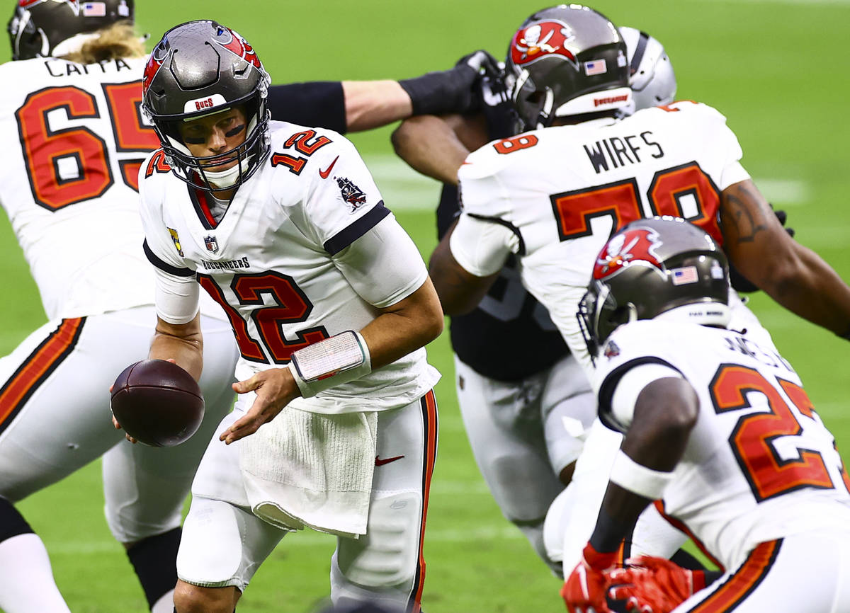 Tampa Bay Buccaneers quarterback Tom Brady (12) looks to hand off the ball to cornerback Sean M ...