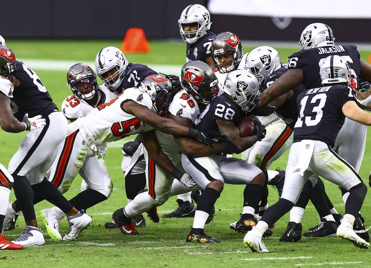 Las Vegas Raiders running back Josh Jacobs (28) gets stopped by Tampa Bay Buccaneers defensive ...
