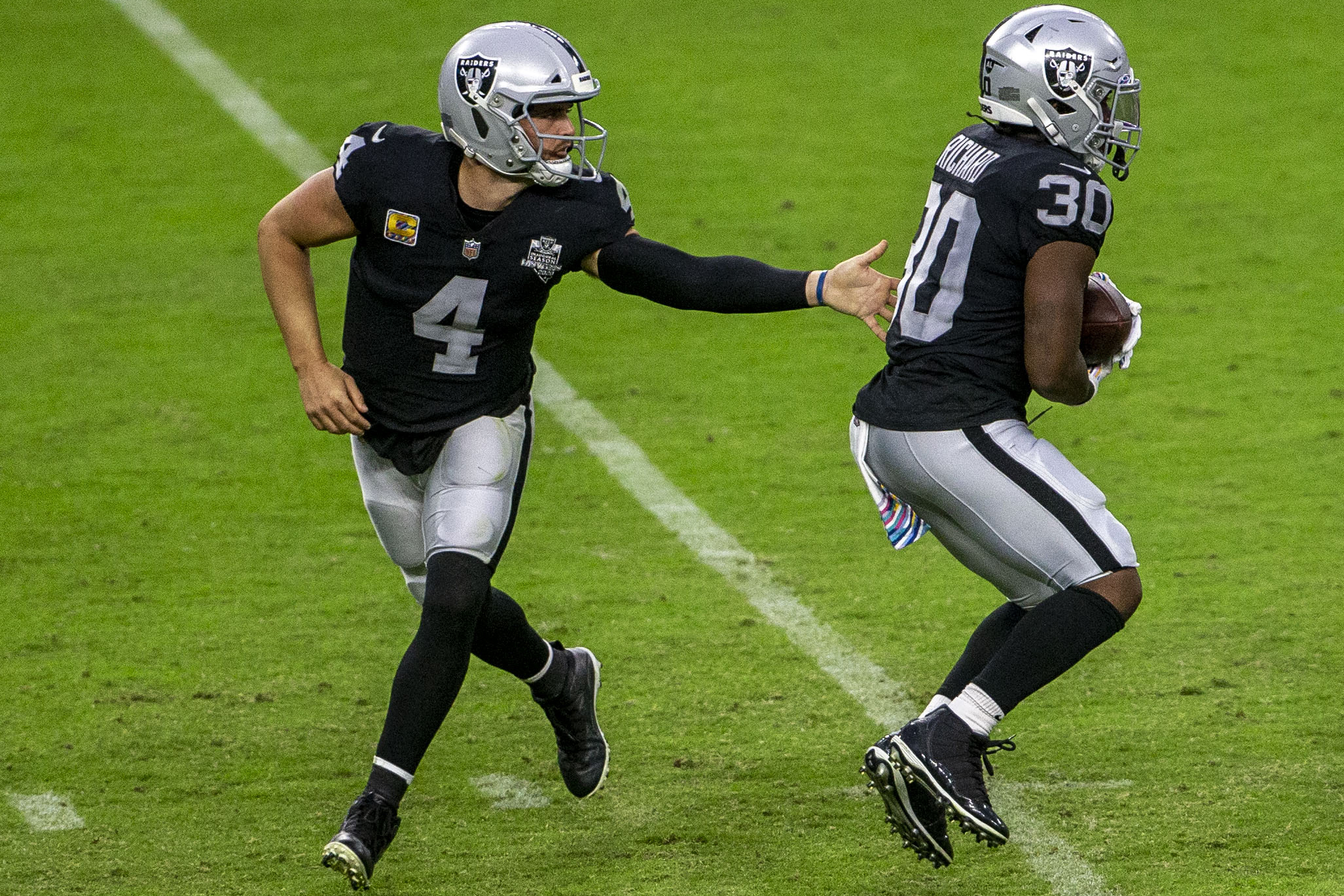 Las Vegas Raiders quarterback Derek Carr (4) hands off the football to running back Jalen Richa ...