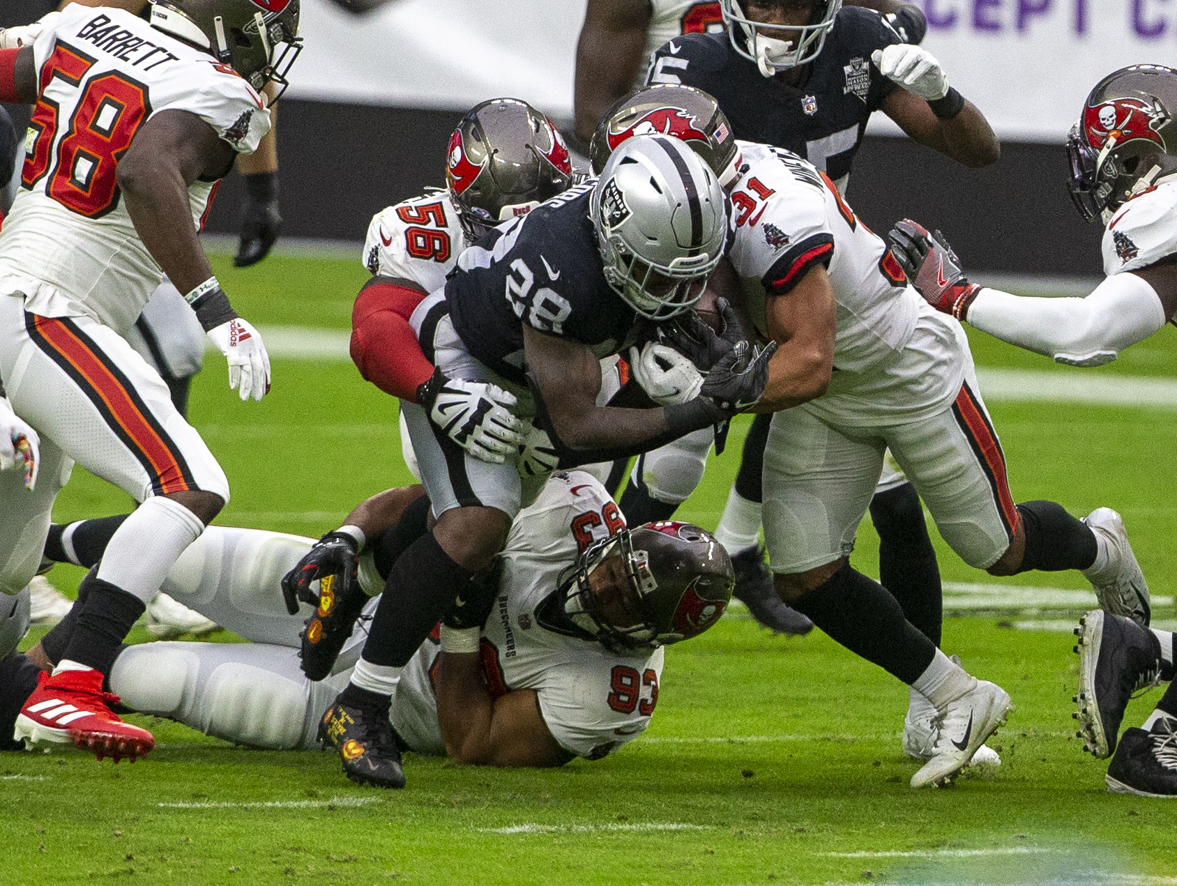 Las Vegas Raiders running back Josh Jacobs (28) is brought down by defensive end Ndamukong Suh ...