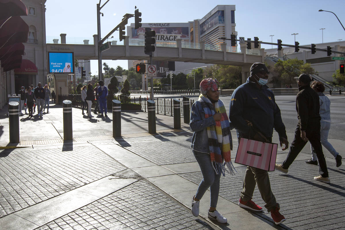 Visitors to the Las Vegas Strip traded their summer attire for hats, scarves and jackets on Mon ...