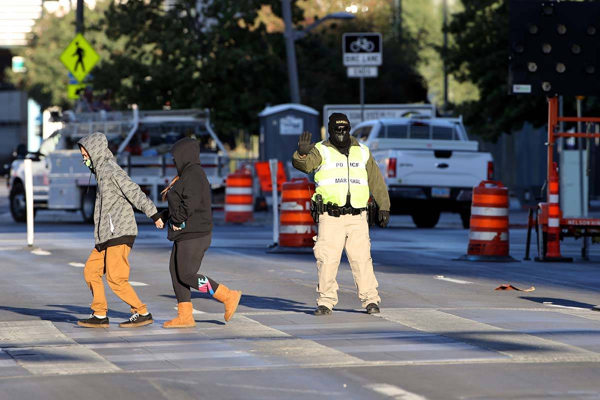 A marshal is bundled up for the chilly weather as he stops traffic for pedestrians crossing Cla ...