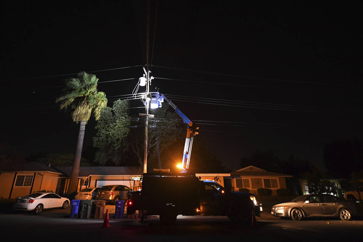 A PG&E lineman works on repairing electrical wires that were touching due to high winds on ...