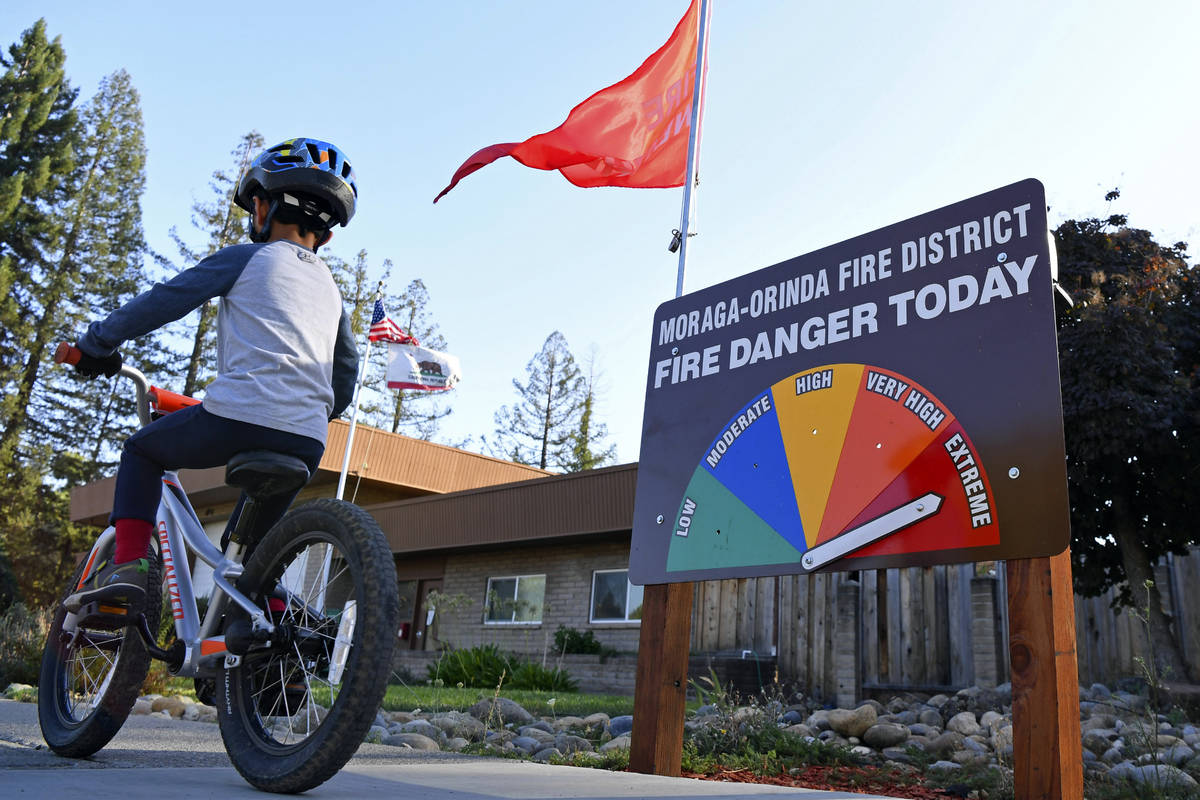 A boy rides his bike past the fire danger meter showing extreme fire danger in front of the Mor ...