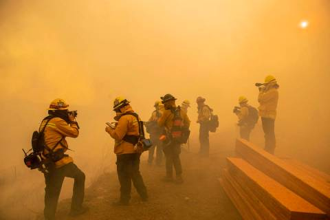 Firefighters with Cal Fire are enveloped in smoke as fire from the Green Fire passes by near ho ...