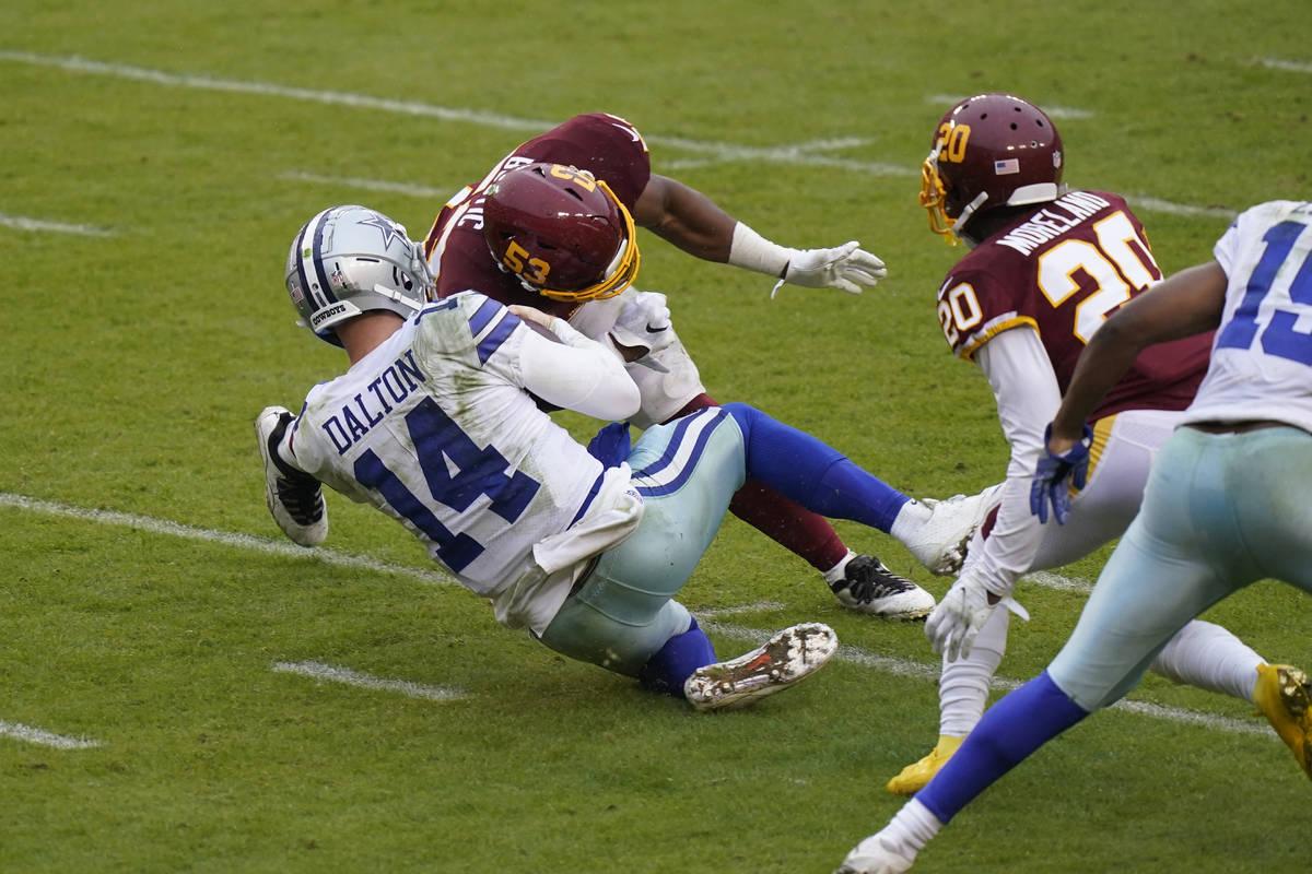 Dallas Cowboys quarterback Andy Dalton (14) is hit by Washington Football Team inside linebacke ...
