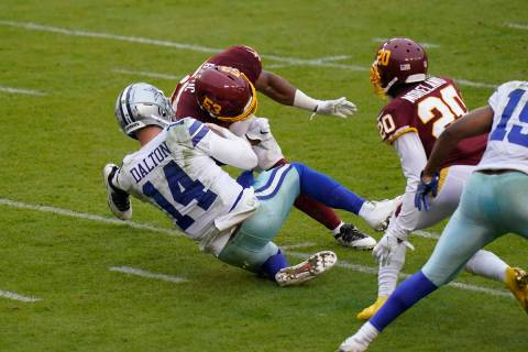 Dallas Cowboys quarterback Andy Dalton (14) is hit by Washington Football Team inside linebacke ...