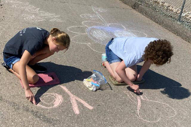 Tarkanian Middle School leadership students chalk the race route for the Candlelighters Superhe ...