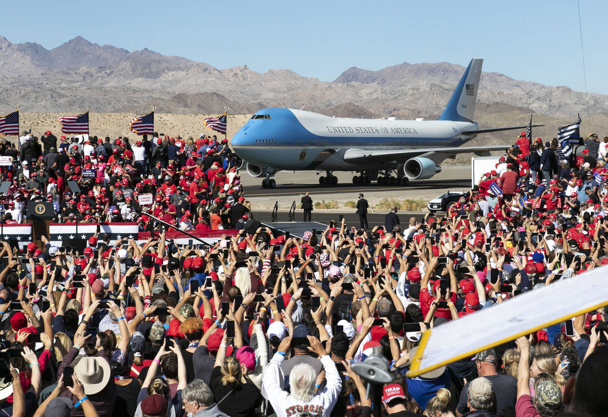 Supporters cheer as Air Force One, carrying President Donald Trump, approaches the stage at Lau ...