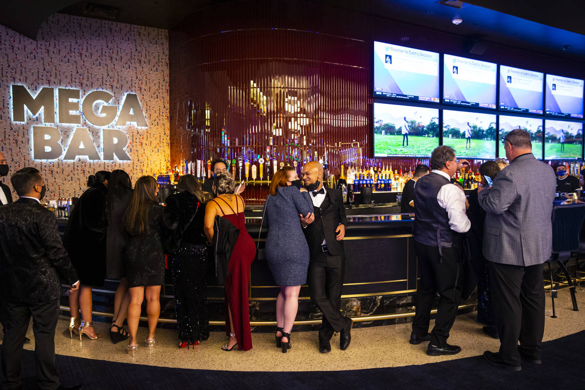 People relax by the Mega Bar at Circa as it opens to the public just after midnight in downtown ...