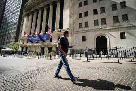 A pedestrian pass the New York Stock Exchange, Friday, Oct. 2, 2020, in New York. Stocks aroun ...