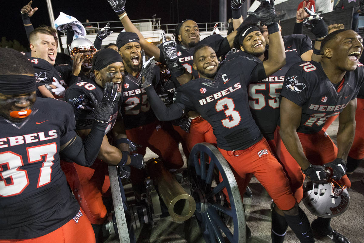 UNLV celebrates with the Fremont Cannon after defeating the Nevada Wolf Pack 34-29 following an ...