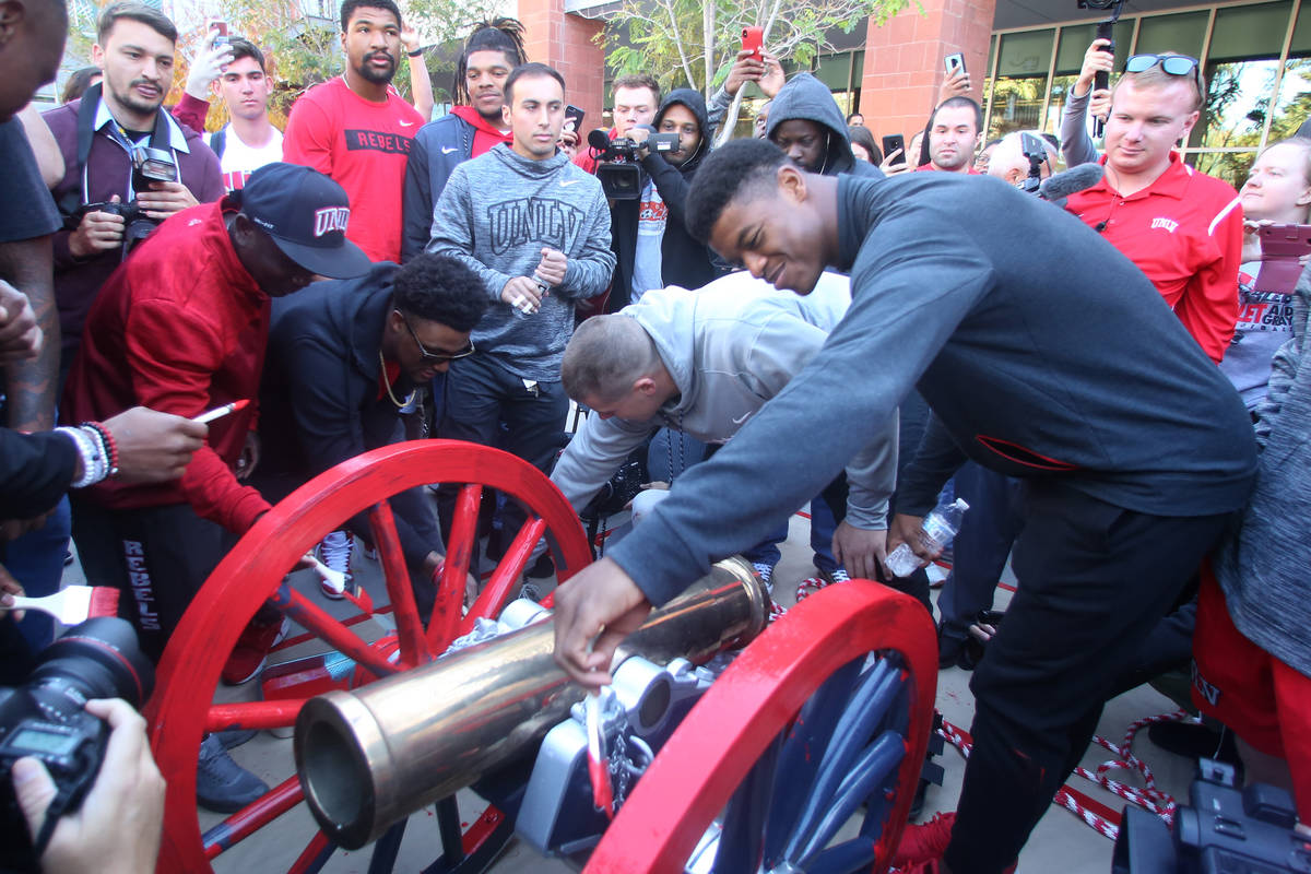 UNLV students and officials watch as UNLV's football players, including linebacker Javin White, ...