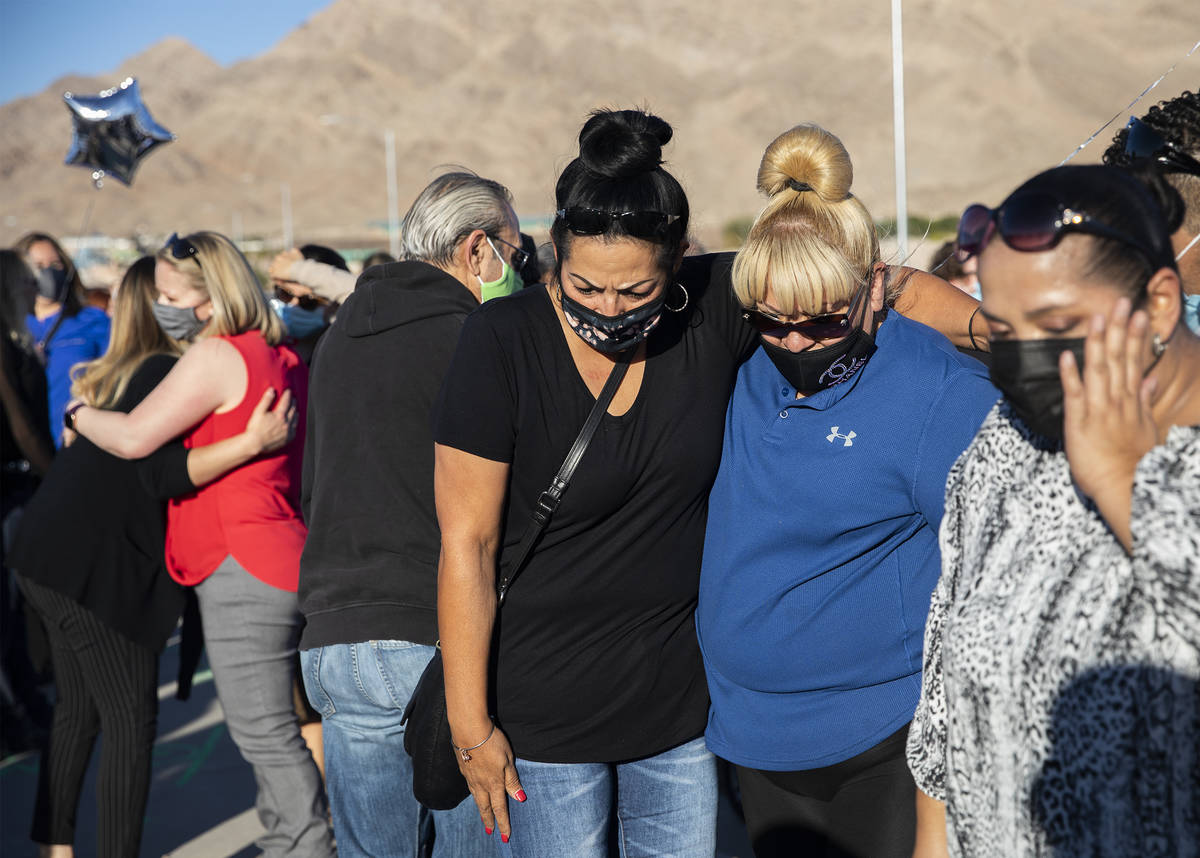 Martha Flores, left, and Laura Pi–a, right, comfort each other as they pay respects to t ...