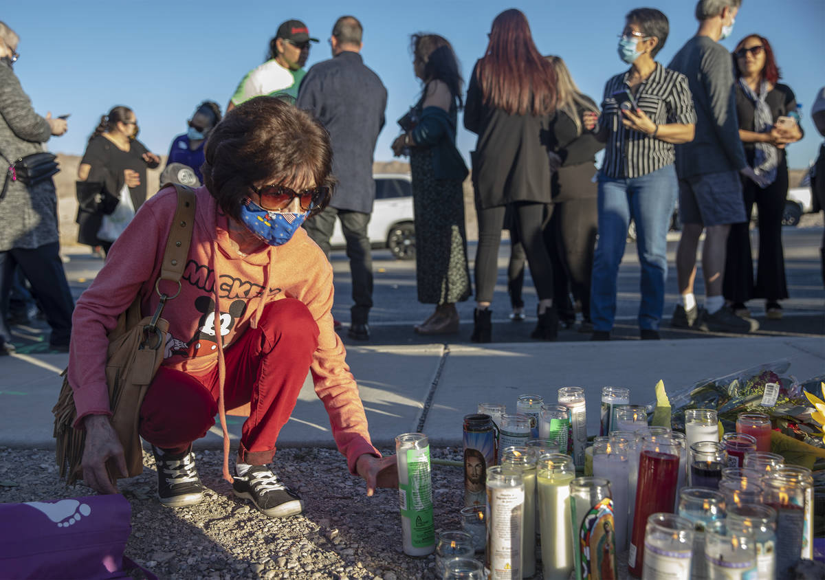 Karen Reda places a candle at a makeshift memorial in honor of her sister Michelle Weissman, a ...
