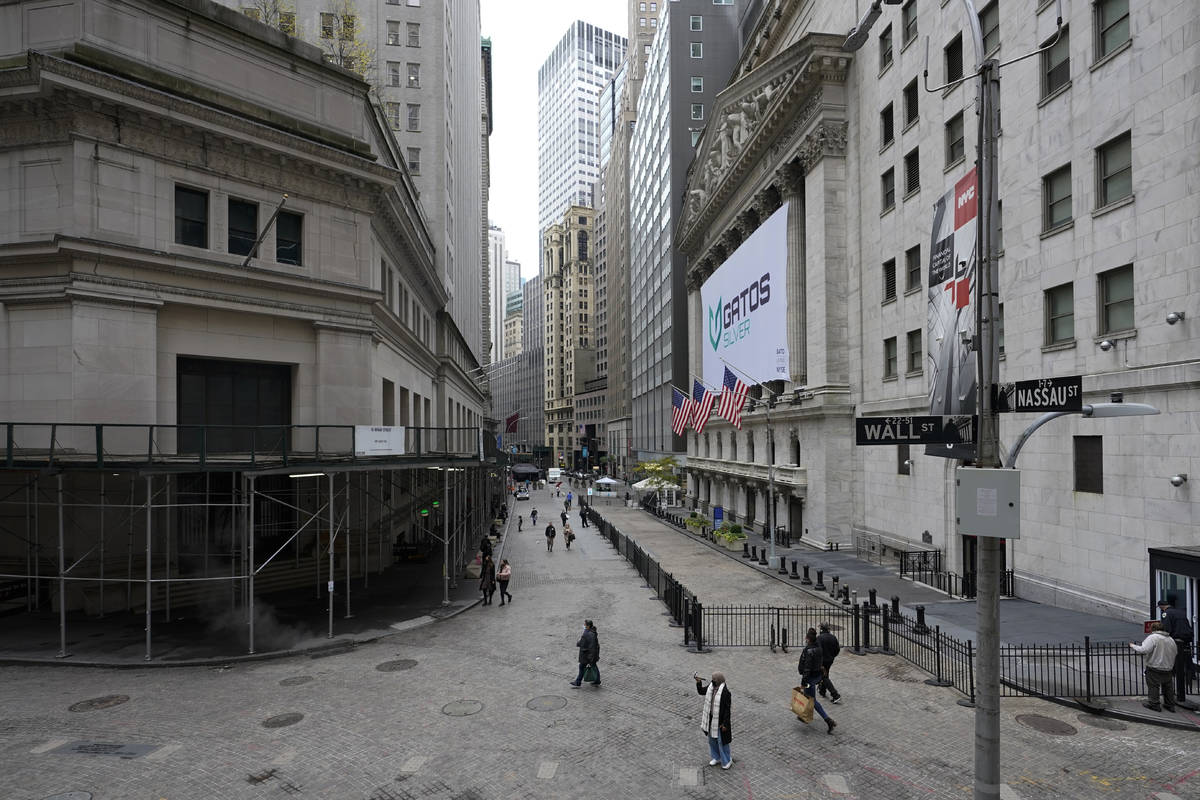 Visitors to the financial district walk past the New York Stock Exchange, Wednesday, Oct. 28, 2 ...
