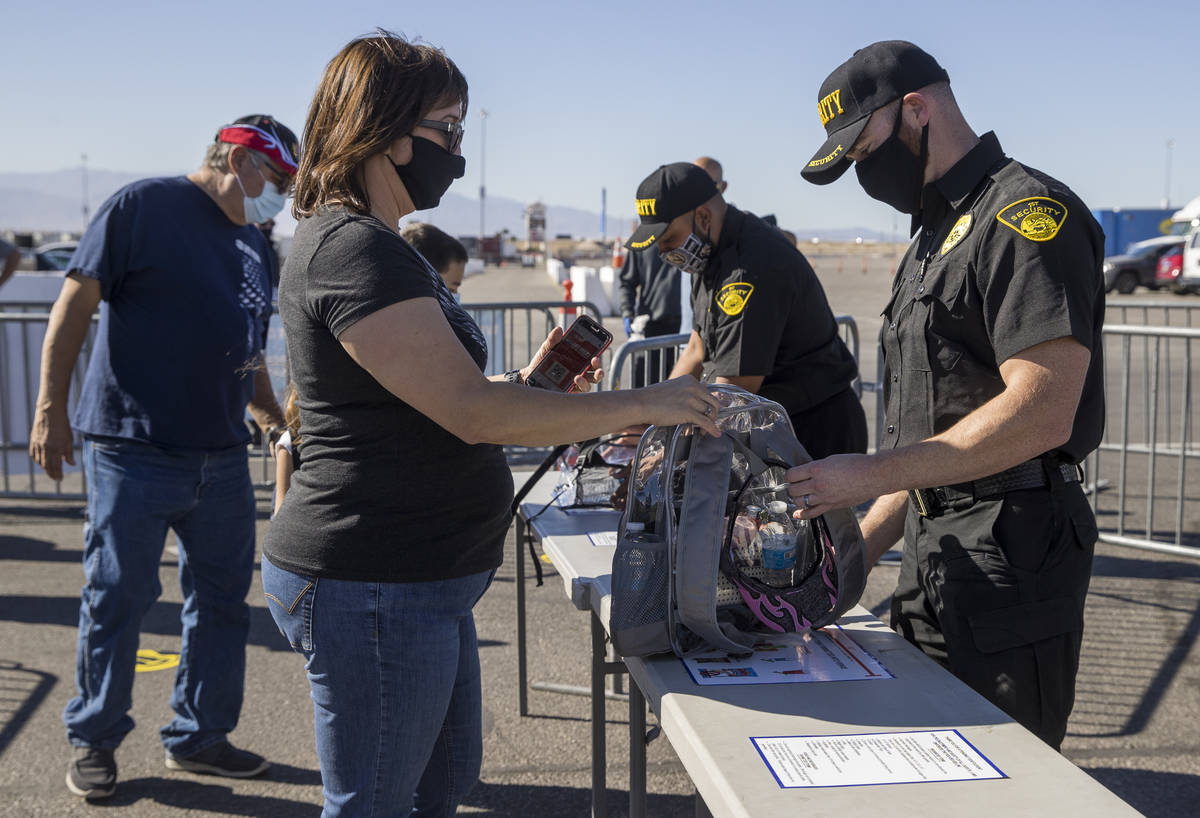 Fan Rose Jaramillo, center, has he bag checked by security as the Las Vegas Motor Speedway host ...