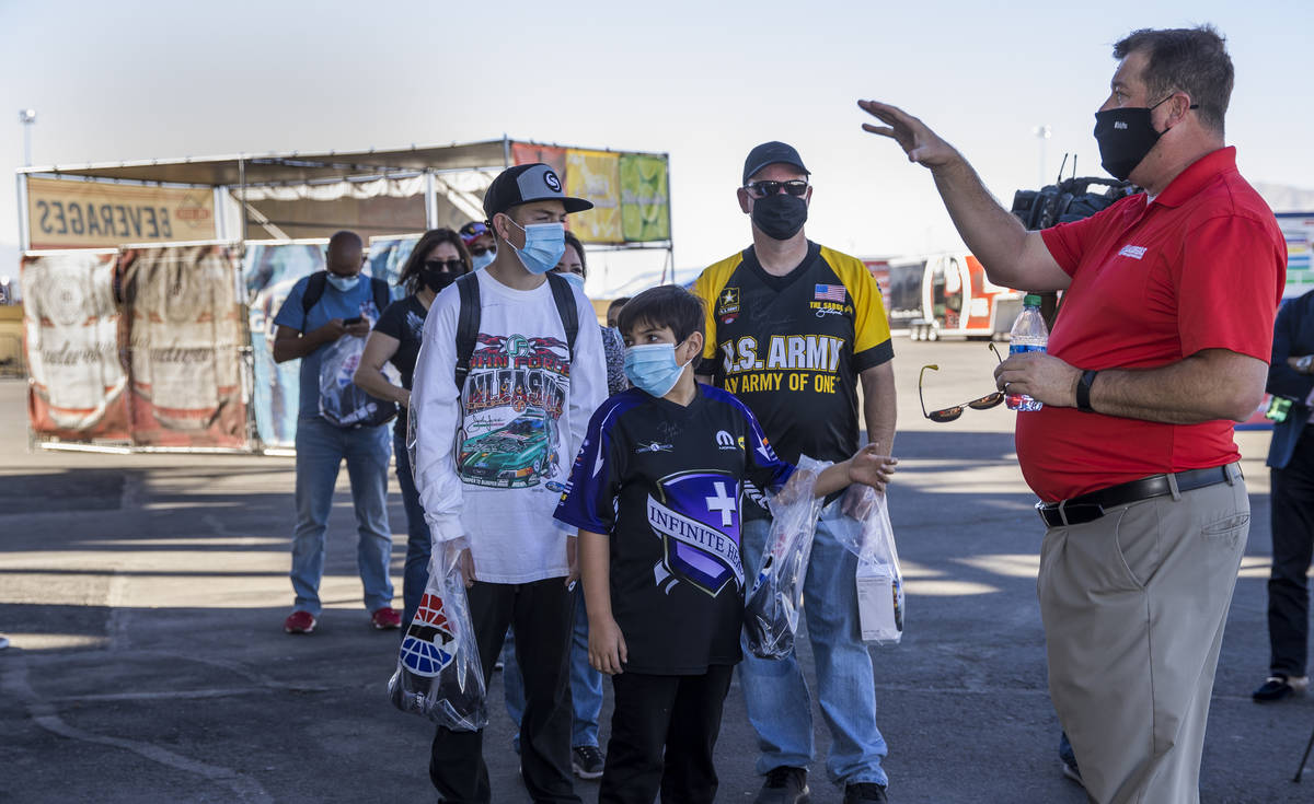 (From right) Jeff Motley with the Las Vegas Motor Speedway instructs fans Eric, Ben, 10, and Co ...