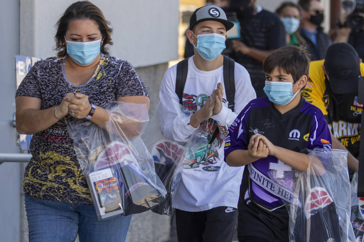 (From left) Vanessa, Cody, 14, and Ben, 10, Roberts use some hand sanitizer as the family walks ...