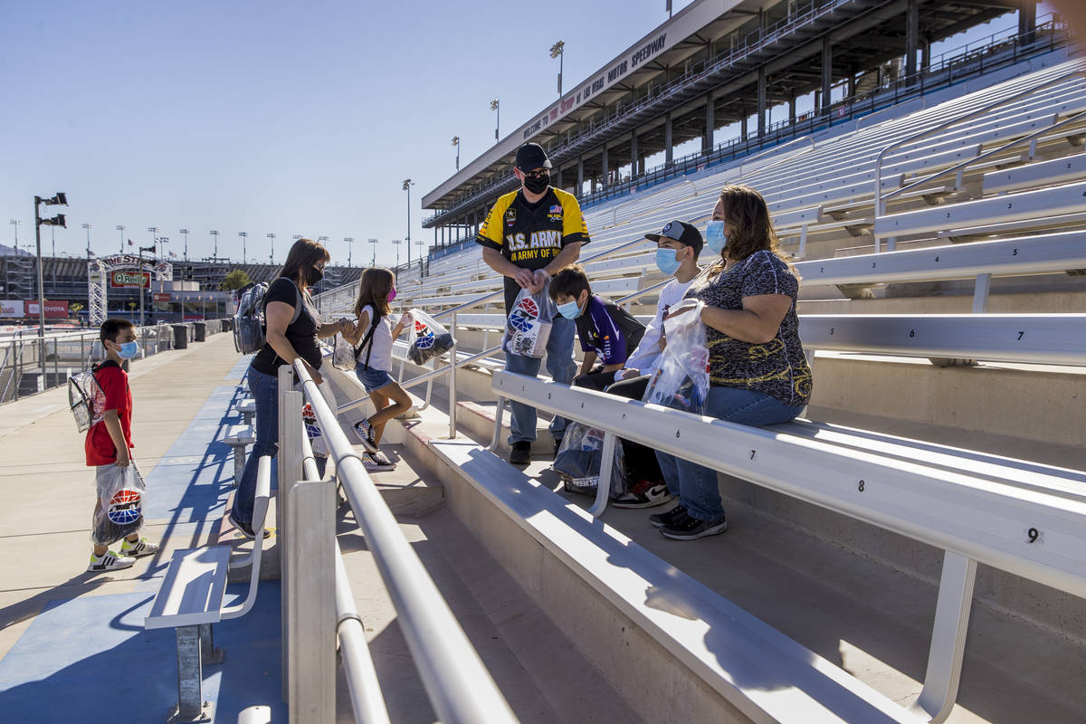 (From left) The Jaramillo and Roberts families enter the stands about the track as the Las Vega ...