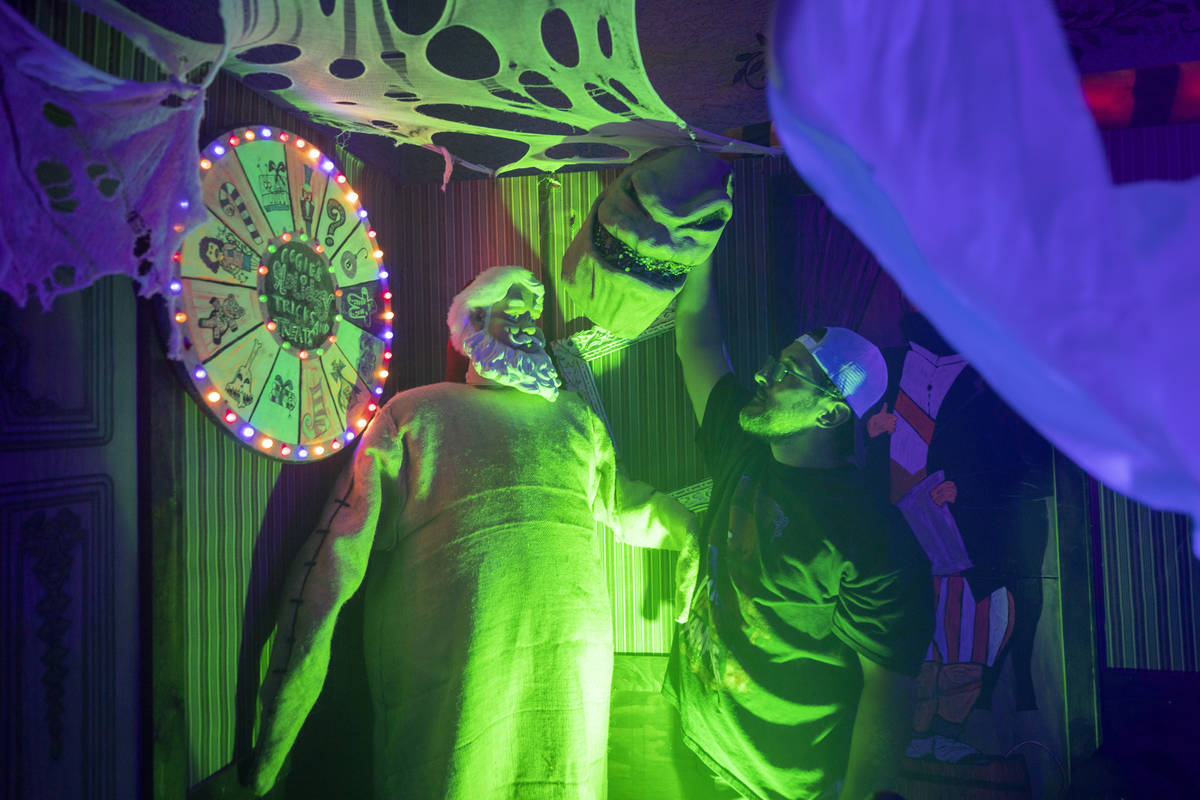 Leroy Garcia takes off Santa's costume that is placed in his family's Haunted Mansion inspired ...