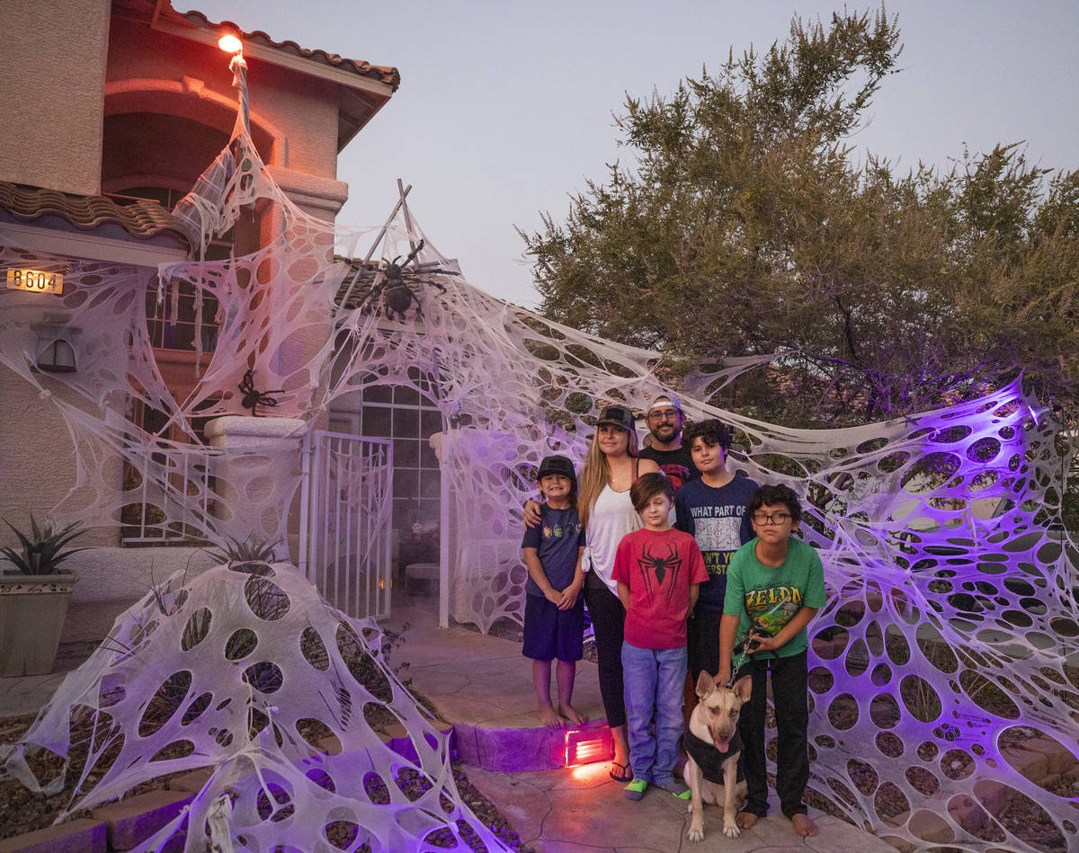 Tiffany and Leroy Garcia are photographed with their four sons in front of their Disney inspire ...