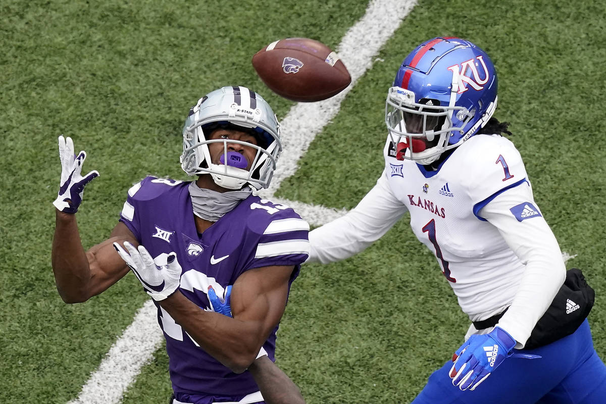 Kansas State wide receiver Chabastin Taylor (13) catches a long pass under pressure from Kansas ...