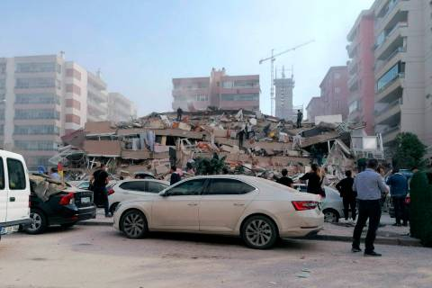 People work on a collapsed building, in Izmir, Turkey, Friday, Oct. 30, 2020, after a strong ea ...