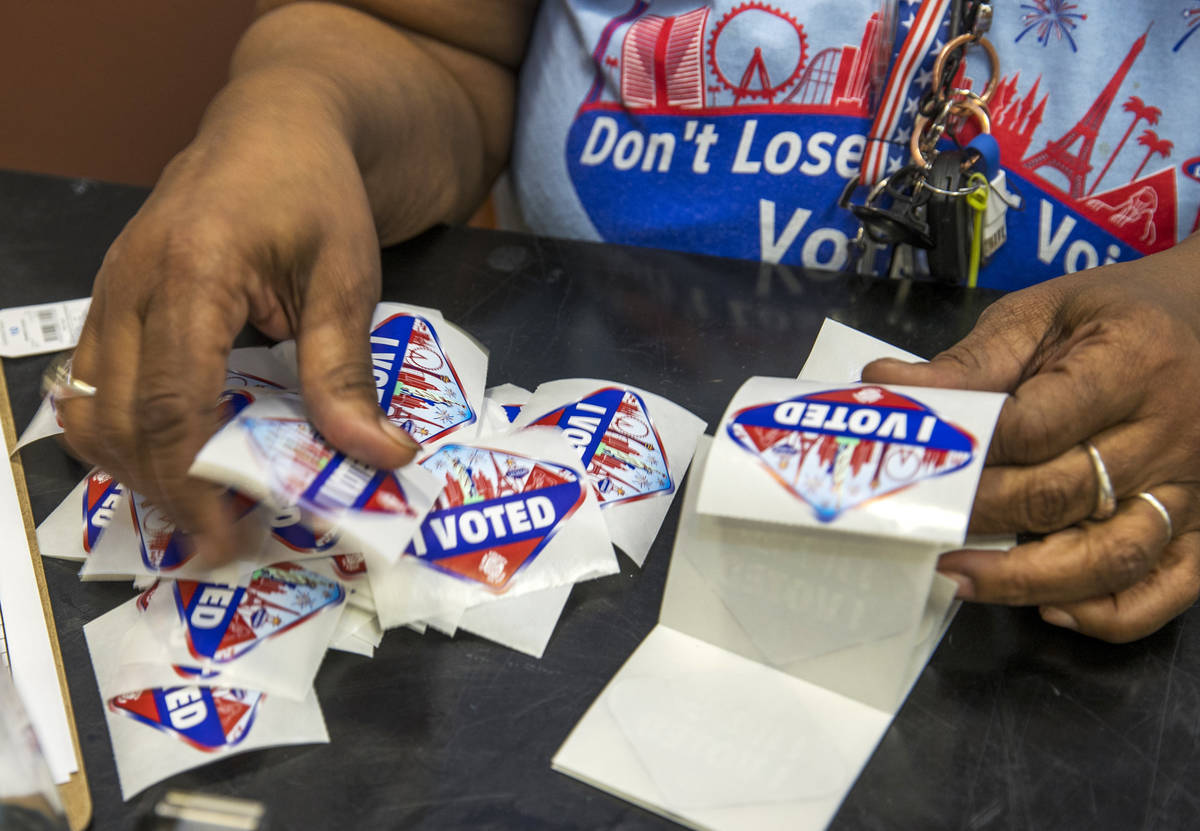 Elections worker Robin Wright readies ÒI VotedÓ stickers for mail-in ballot drop off ...