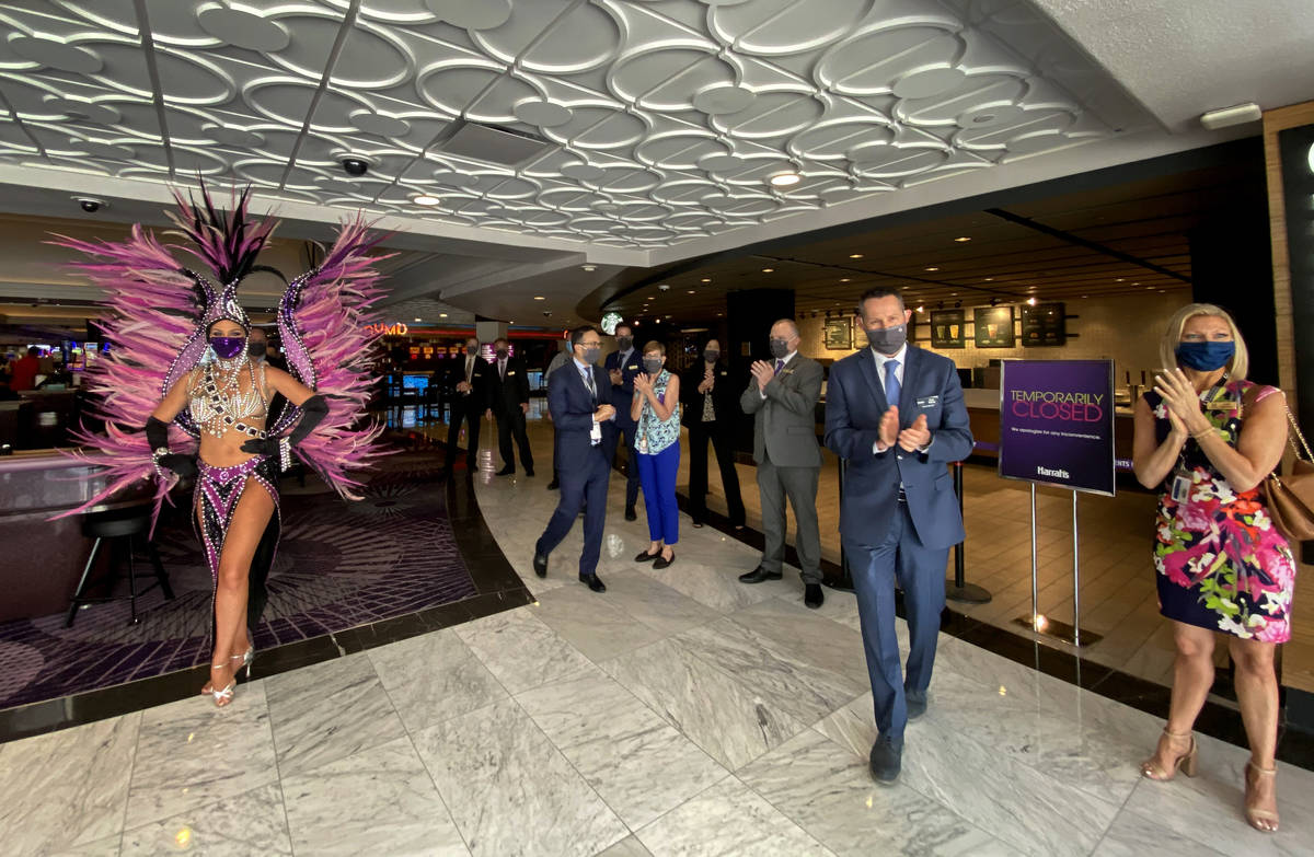 Staff and showgirls greet guests arriving as the doors at Harrah's are open for business again ...