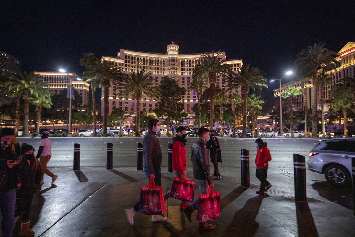 Tourists walk down Las Vegas Blvd., on the Strip, Friday, Nov. 27, 2020, in Las Vegas. (Elizabe ...