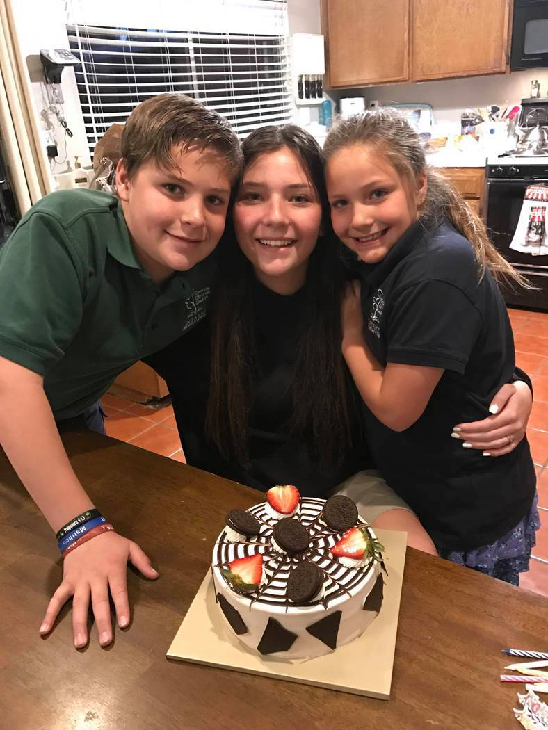 Micaela Miller, 15, center, Noah Miller,11, left, and Madison Miller, 8, made a cake for their ...