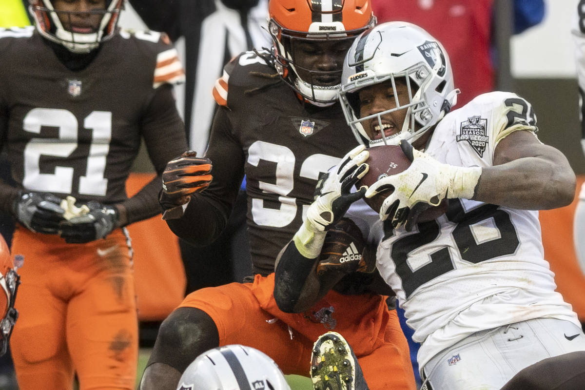 Las Vegas Raiders running back Josh Jacobs (28) fights for extra yardage with Cleveland Browns ...