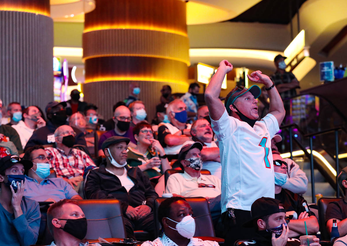 Ted Morrison, of Las Vegas, stands and cheers while watching the Los Angeles Rams face off the ...