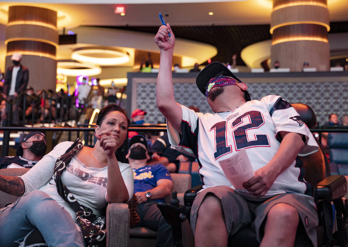 """Rachel Randall, left, and her friend Jesus """"Chuy"""" Baca, right, watch NFL Sunday at the new ..."""