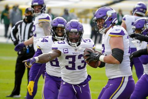 Minnesota Vikings' Ezra Cleveland (72) helps Dalvin Cook (33) celebrate his touchdown run durin ...