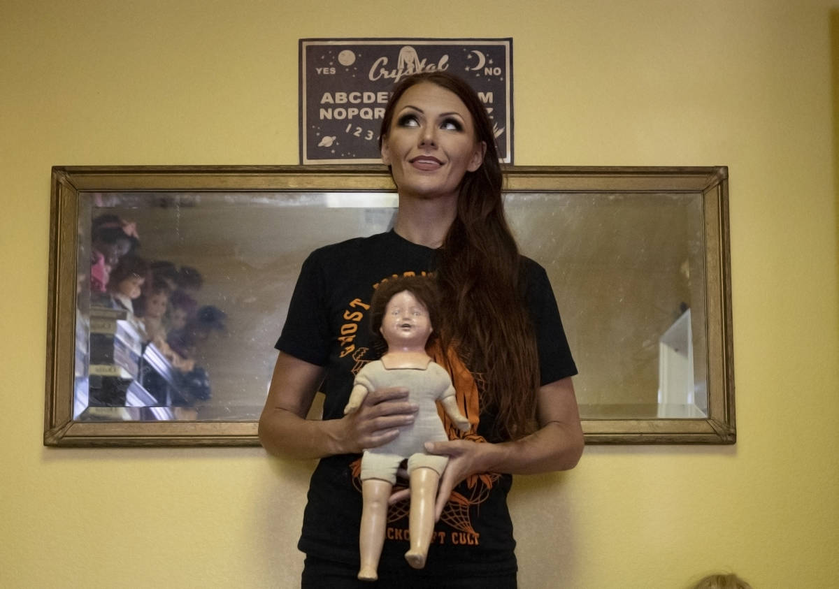 Paranormal enthusiast Staysha Randall is seen in front of a haunted mirror holding a doll with ...