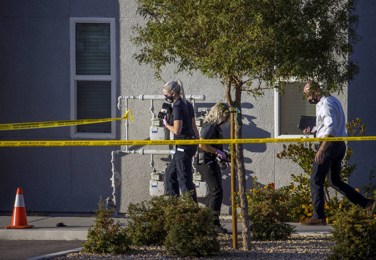 Crime scene investigators document the scene outside after four were killed and one injured in ...