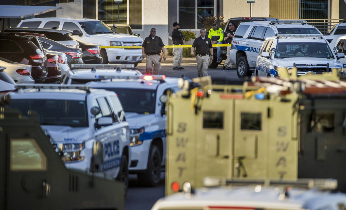 Officers move about outside after four were killed and one injured in police shooting at The Do ...