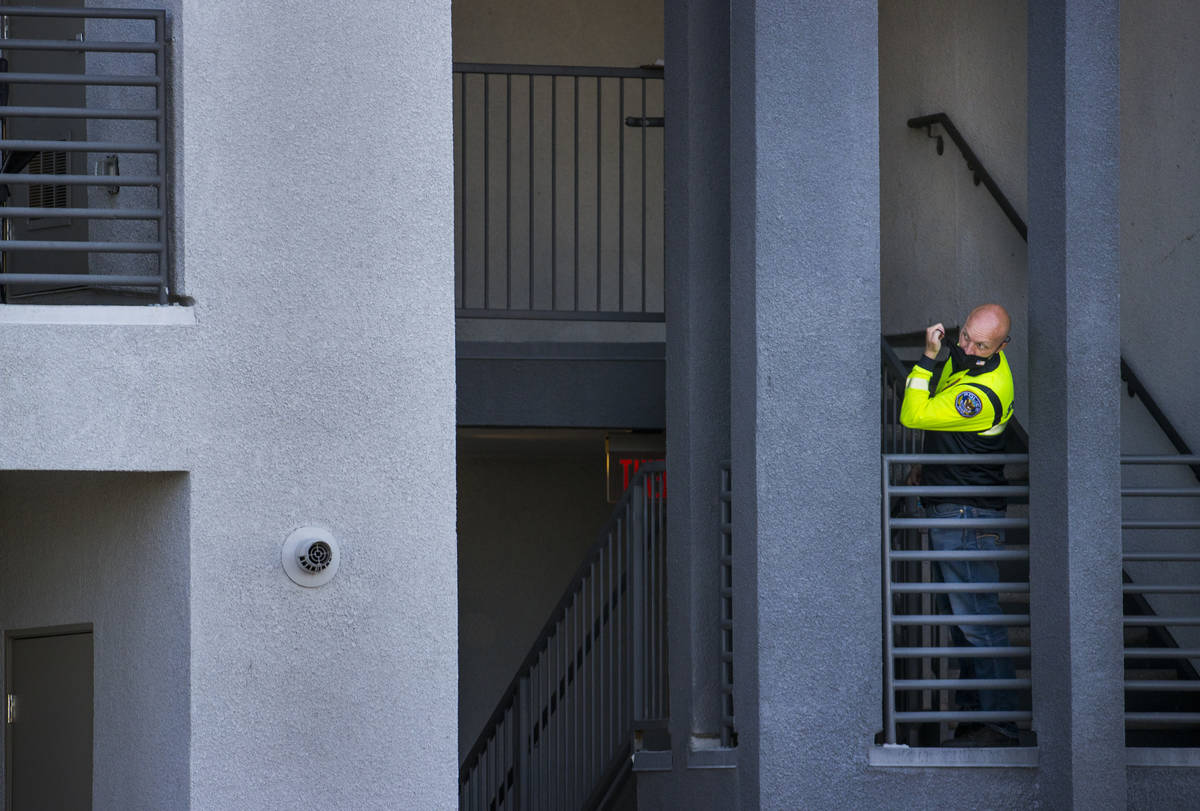 An officer looks out from a stairwell after four were killed and one injured in police shooting ...