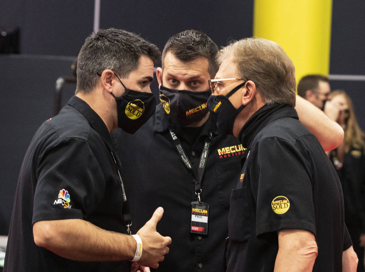 Bidder assistants Jordan Hunter, left, Paul Guck, and Tim Phillips, right, discuss prior to the ...