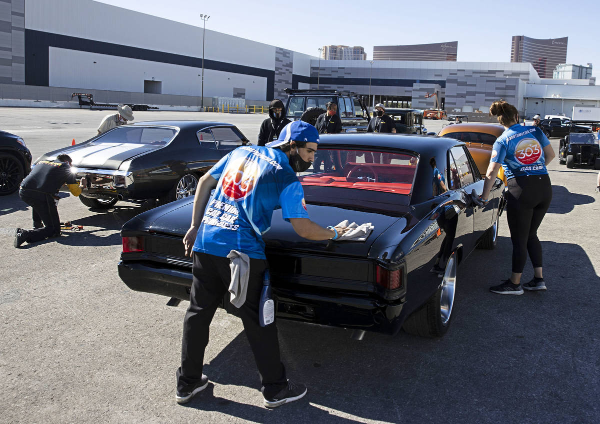 Auto detailer Max Zabata, center, details a 1967 Chevy Malibu as cars are lined up to be inspec ...
