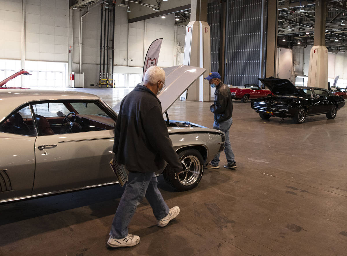 Guests, who declined to give their names, check out a 1969 Chevy Camaro at the Las Vegas Conven ...
