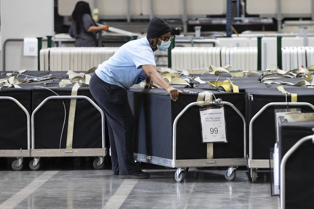 A Clark County election worker arranges voting machines at the Election Center on Wednesday, No ...
