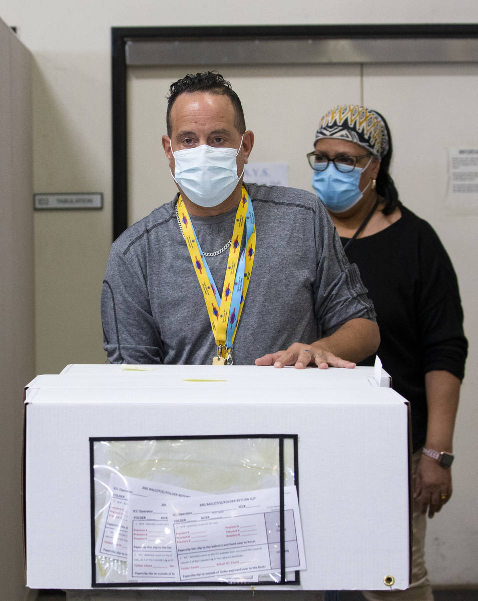 Clark County Election Center employees wheel in mail-in ballots to be counted the day after Ele ...